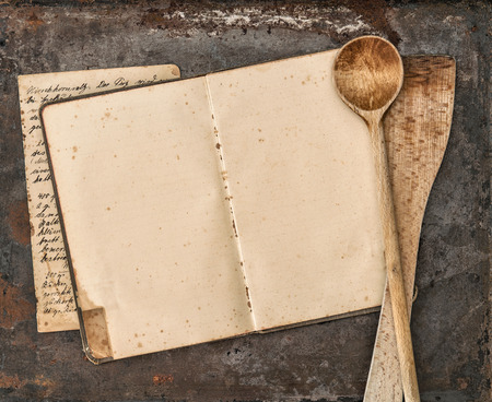 Vintage handwritten recipe book and old kitchen utensils on rustic metal background. Retro style toned picture Foto de archivo