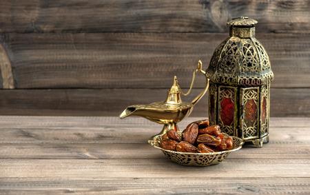 comida arabe: L�mpara de Ramad�n y las fechas en el fondo de madera. Bodeg�n festivo con linterna oriental