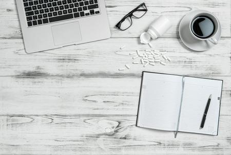 cansancio: Lugar de trabajo de oficina con el libro calendario, taza de cápsulas de café, informática y medicina. El estrés y el cansancio concepto. Imagen de tonos azul Foto de archivo