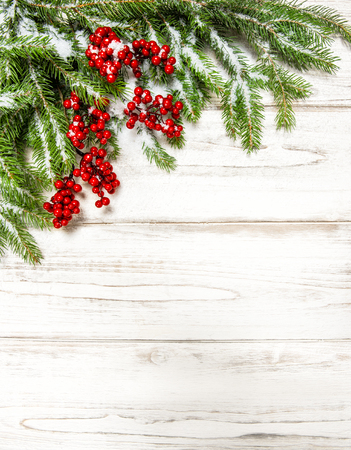 christmas snow: Christmas tree branch with red berries on wooden background. Winter holidays decoration