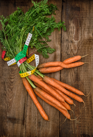 measurement tape: Carrots with measurement tape on wooden background.