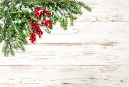 evergreen branch: Rama de un árbol de Navidad con bayas rojas de fondo de madera. Foto de archivo
