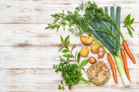 Vegetables mix for preparation of  soup. Leek, carrots, onion, parsley, potatoes, celery root, bay laurel leaves. Stock Photo