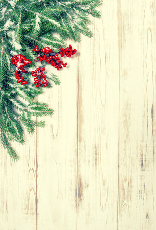 retro frame: Christmas tree branch with red berries wooden background. Stock Photo