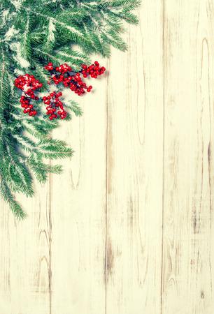 marcos decorados: Rama de un �rbol de Navidad con bayas rojas de fondo de madera. Foto de archivo