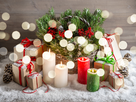 basket: Christmas still life with burning candles and gift box. Festive decoration. Vintage style tones picture with lights effect Stock Photo
