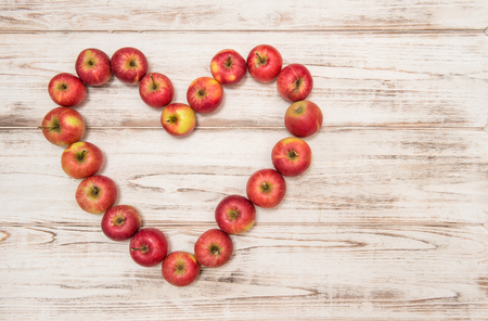 love hearts: Apples in heart shape on rustic wooden background. Stock Photo