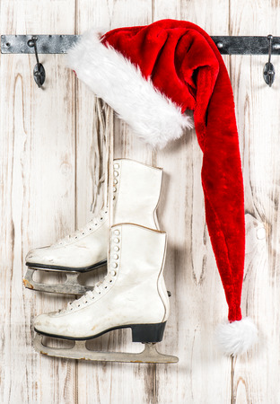 stock photo vintage christmas decoration red santa claus hat and white ice skates hanging over rustic wooden background