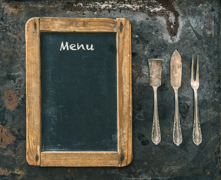 antique background: Antique silver cutlery and blackboard with sample text Menu. Vintage style toned picture. Stock Photo