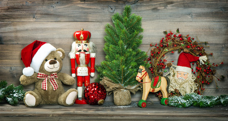 retro christmas: Vintage Christmas decoration Teddy Bear, Rocking Horse and Nutcracker. Retro style colored photo with vignette