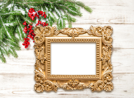 Christmas decoration with golden picture frame on wooden background. Winter holidays