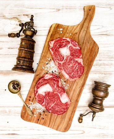 rib eye: Raw fresh meat Rib eye Steak with kitchen utensils on wooden desk.