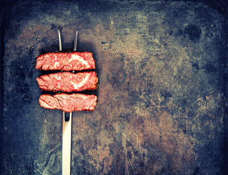 bbq grill: Grilled beef meat on rustic metal background. Food concept. Vintage style toned picture