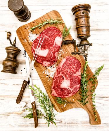 rib eye: Raw fresh meat Rib Eye Steak with herbs on wooden background. Stock Photo
