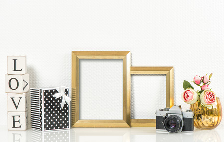 no name: Golden picture frames, rose flowers and no name vintage photo camera. Retro style decorations