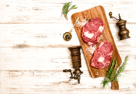 rib eye: Raw fresh meat Rib eye Steak with herbs and spices on wooden desk.