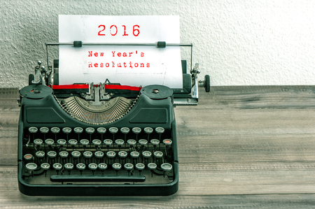 antique background: Typewriter with white paper page on wooden table. sample text 2016 New Years Resolutions. vintage style toned picture Stock Photo