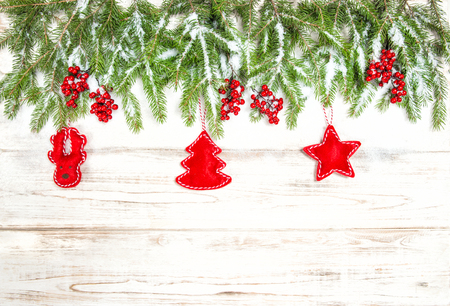 hollyberry: Christmas tree branches with red handmade toys decoration on bright wooden background.