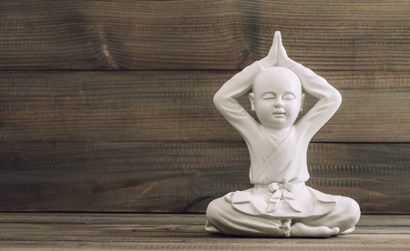 lotus pose: White buddha. Monk sculpture on wooden background. Meditation and relax Stock Photo