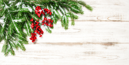 hollyberry: Christmas decoration border. Fir tree branch with red berries and snow on wooden background