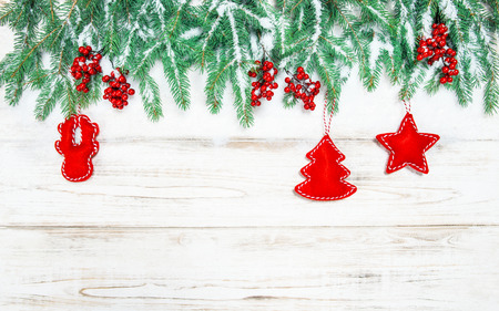 hollyberry: Christmas tree border with red decorations. Holidays background. Vintage style toned picture