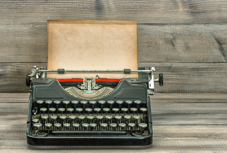 Antique typewriter with grungy paper on wooden background. Retro style toned picture. Selective focus