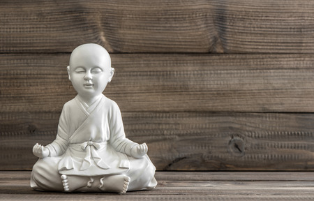 zen: Sitting buddha. White statue on wooden background. Relaxing concept