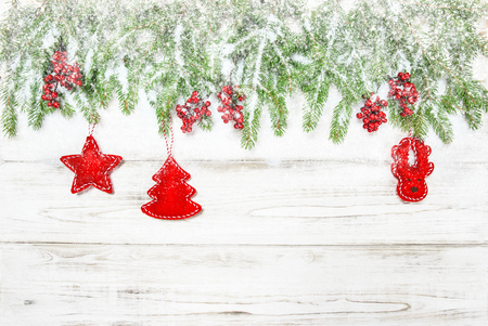 hollyberry: Christmas background. Evergreen tree branch with red decoration and falling snow