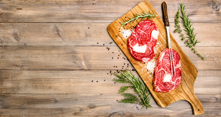 rib eye: Raw beef meat Rib Eye Steak with herbs and spices on wooden kitchen desk. Food background