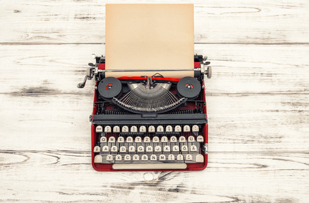 Old typewriter on wooden table. Antique object. Vintage style toned picture. German lettering