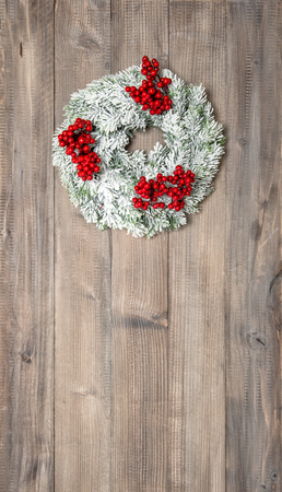 hollyberry: Christmas wreath with red berries over wooden background. Festive decoration