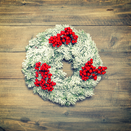 hollyberry: Christmas wreath with red berries over wooden background. Festive decoration. Vintage style toned picture Stock Photo