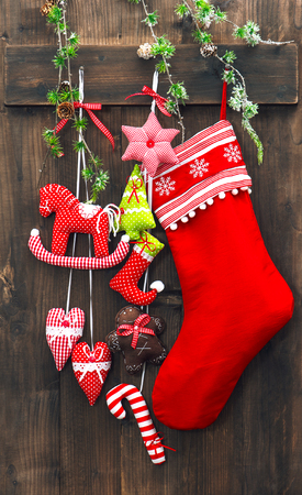 branch of a christmas tree: Christmas decoration stocking and handmade toys over rustic wooden background. Festive ornaments