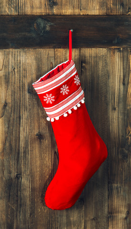 christmas stockings: Christmas stocking. Red sock hanging over rustic wooden background. Holidays decoration Stock Photo