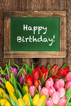 text space: Tulip flowers and vintage green chalkboard. Sample text Happy Birthday!