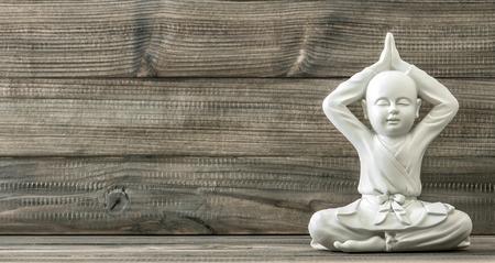 Sitzender Buddha. Weiß Mönch Statue auf Holzuntergrund. Vintage-Stil getönten Bild Standard-Bild - 48991852