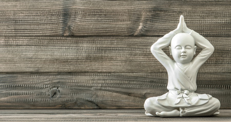 Sitting buddha. White monk statue on wooden background. Vintage style toned picture Stockfoto
