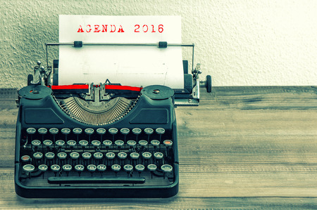 writer: Typewriter with white paper page on wooden table. Sample text AGENDA 2016. Vintage style toned picture Stock Photo
