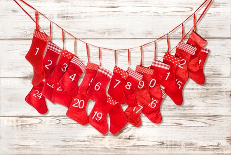 adviento: Calendario de adviento. La decoración de Navidad media roja sobre fondo de madera brillante