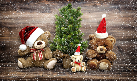 Christmas decoration with funny toys Teddy Bear family. Vintage style toned picture with falling snow effect Standard-Bild