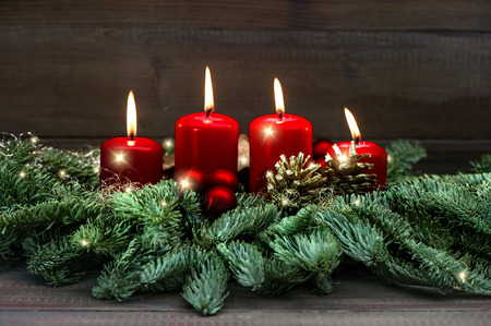 advent candles: Advent decoration wreath with four red burning candles and light effects. Holidays background. selective focus