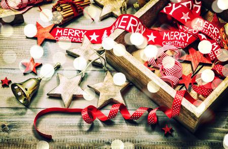 クリスマスの装飾と素朴な木製の背景の装飾。光の効果とレトロなスタイルの暗い色の画像