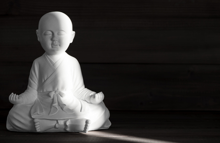 thai decor: White monk statue. Sitting buddha. Meditation and relaxing concept