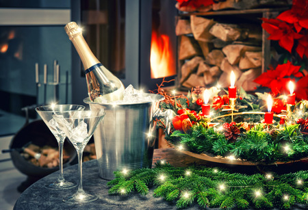 new year: Candlelight dinner. Festive christmas and new year decoration with bottle of champagne and fireplace. Retro style toned picture Stock Photo