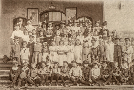 old time: Antique portrait of school classmates. Group of children and teachers outdoors. Vintage picture with original film grain and blur