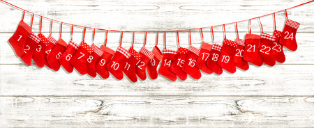 Advent calendar 1-24. Christmas decoration red stocking over bright wooden background
