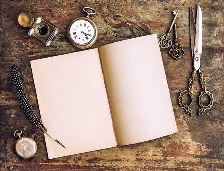 open diary: Open diary book and antique writing tools on wooden background. Vintage style toned picture Stock Photo