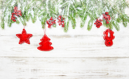 hollyberry: Christmas background. Spruce tree branches with red decoration and falling snow