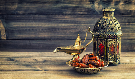 dry food: Ramadan lamp and dates on wooden background. Still life with oriental lantern. Vintage style toned picture
