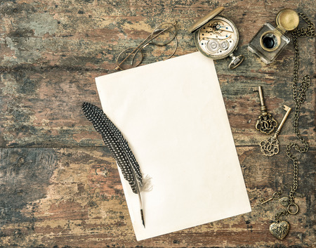 antique paper: Aged paper and antique writing accessories. Feather pen and inkwell on wooden background. Vintage style toned picture Stock Photo